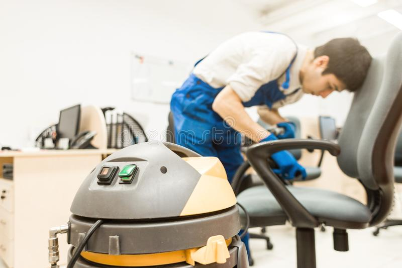 Il giovane in abiti da lavoro ed in guanti di gomma pulisce la sedia dell'ufficio con attrezzatura professionale fotografie stock