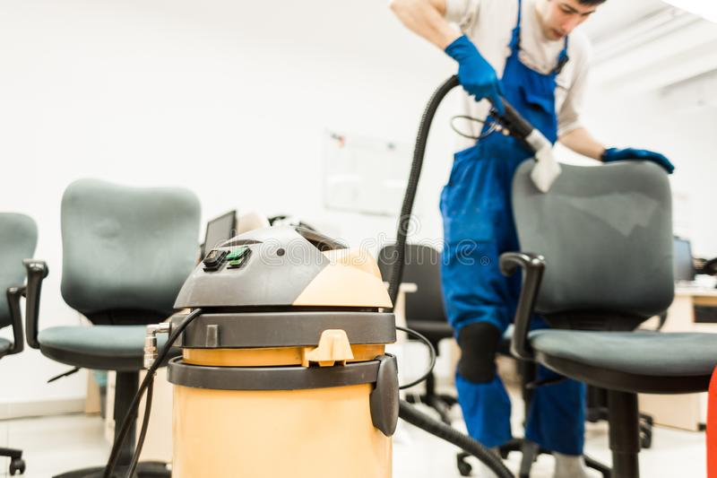 Il giovane in abiti da lavoro ed in guanti di gomma pulisce la sedia dell'ufficio con attrezzatura professionale fotografia stock libera da diritti