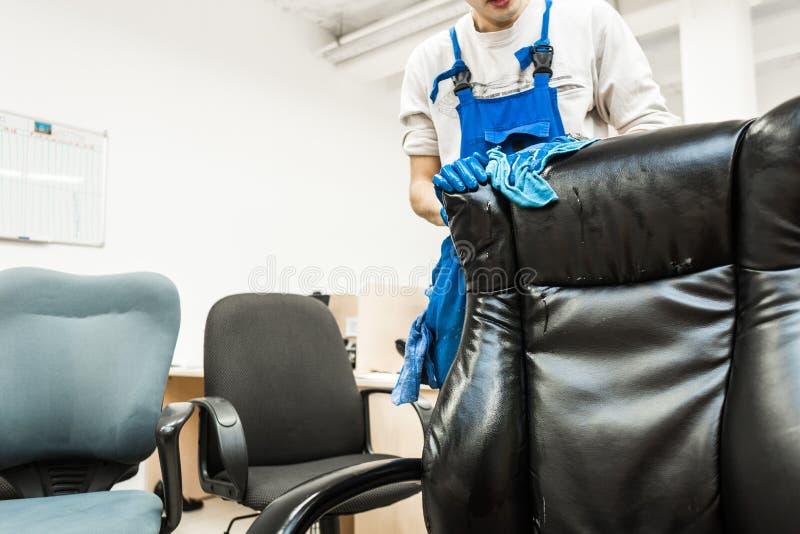 Il giovane in abiti da lavoro ed in guanti di gomma pulisce la sedia dell'ufficio con attrezzatura professionale immagine stock libera da diritti