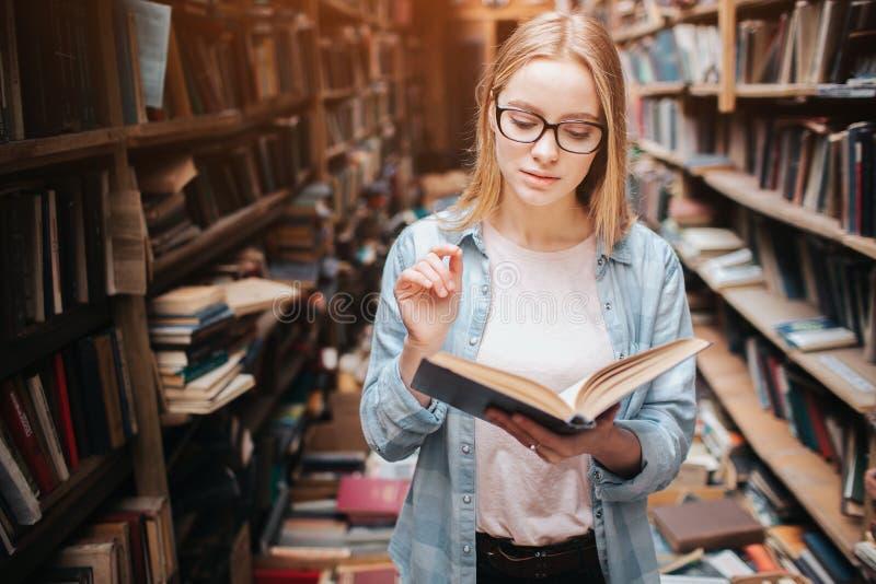 Il giovane adolescente è in biblioteca pubblica Ha trovato un libro e lo ha letto Questa ragazza è pacifico e premuroso calmi fotografie stock