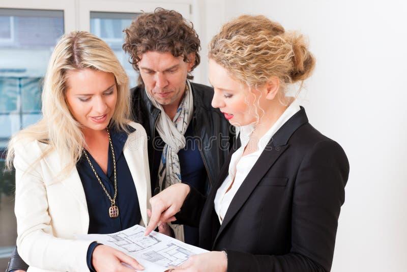 Il giovane agente immobiliare spiega l'accordo di contratto d'affitto coppia fotografie stock libere da diritti