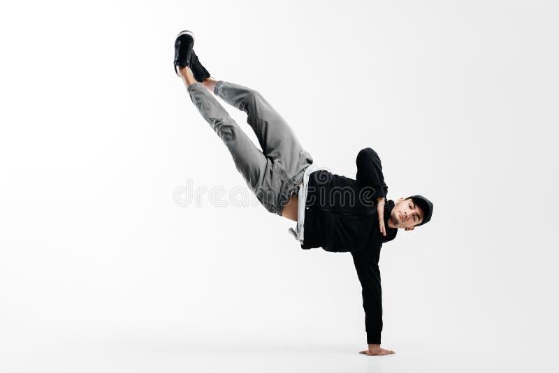 Il giovane alla moda sta ballando le breakdance Sta stando su un braccio e sta sollevando entrambi i vantaggi fotografia stock libera da diritti