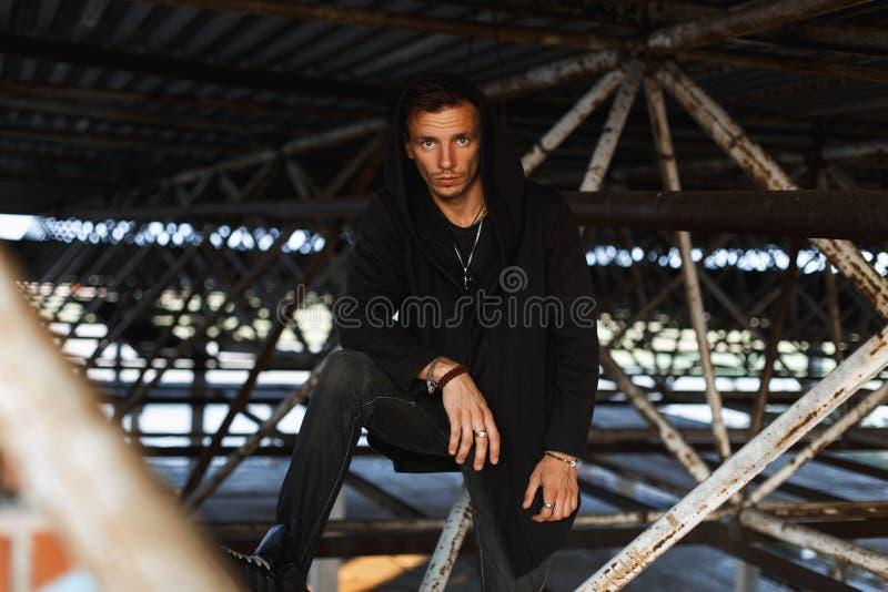 Il giovane alla moda in un cappuccio in abiti neri sta posando immagine stock