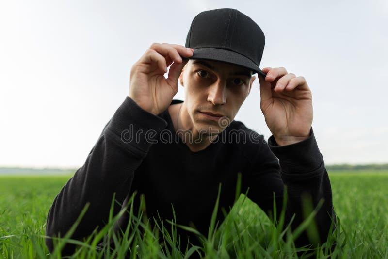 Il giovane alla moda in una camicia nera in un cappuccio d'avanguardia nero regola il suoi cappuccio e resti in erba verde nel ca fotografia stock libera da diritti