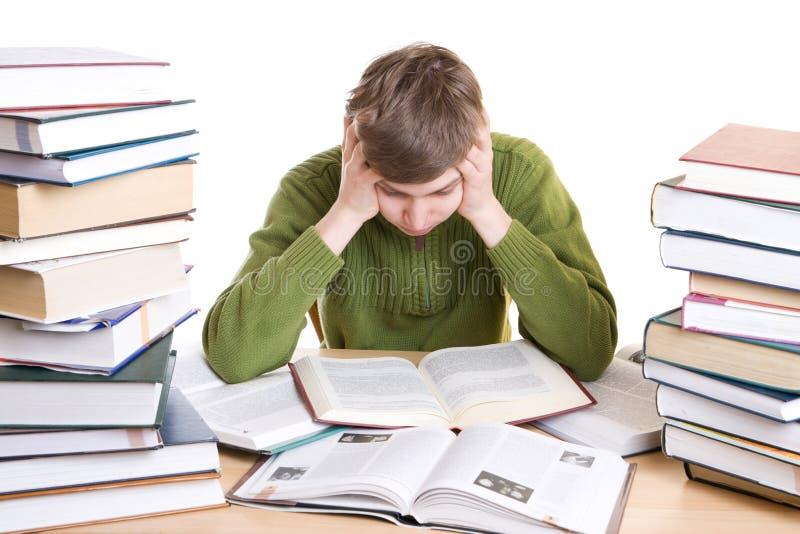 Il giovane allievo con i libri isolati su un bianco fotografie stock