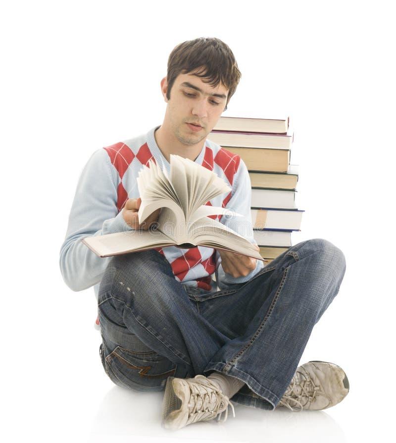 Il giovane allievo con i libri isolati su un whi immagine stock
