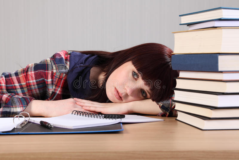 Il giovane allievo si è stancato dalla testa di lavoro sullo scrittorio fotografie stock libere da diritti