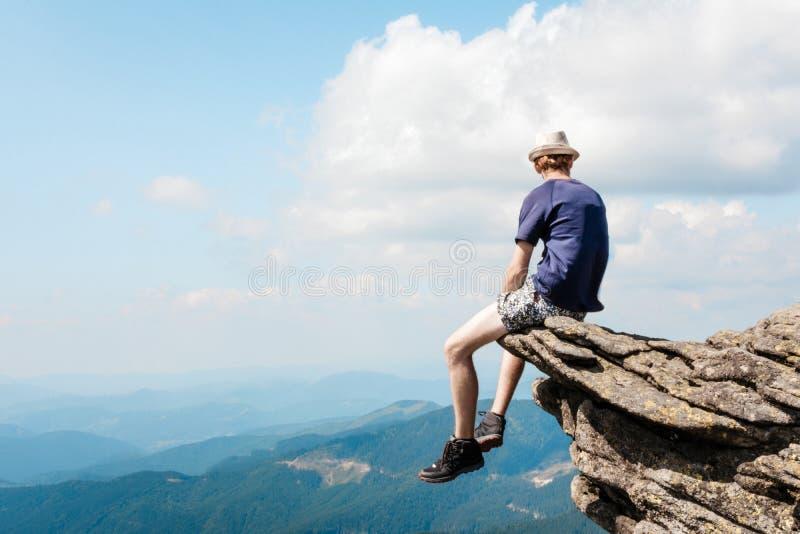 Il giovane ammira il paesaggio della montagna fotografia stock