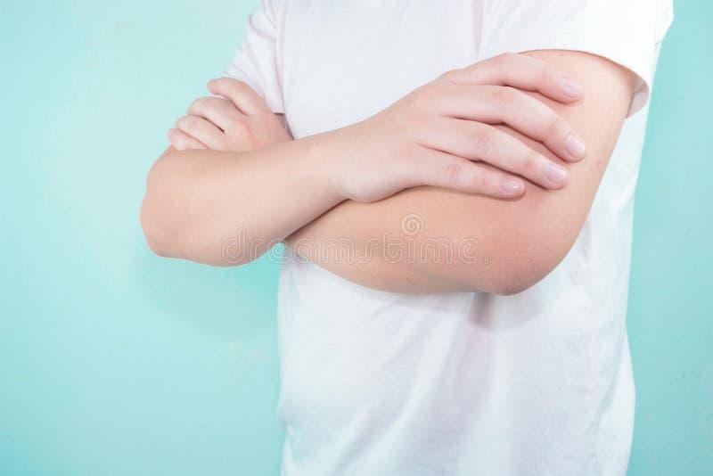 Il giovane asiatico bello che indossa una condizione bianca della maglietta con le armi ha piegato l'isolato su fondo bianco fotografie stock libere da diritti
