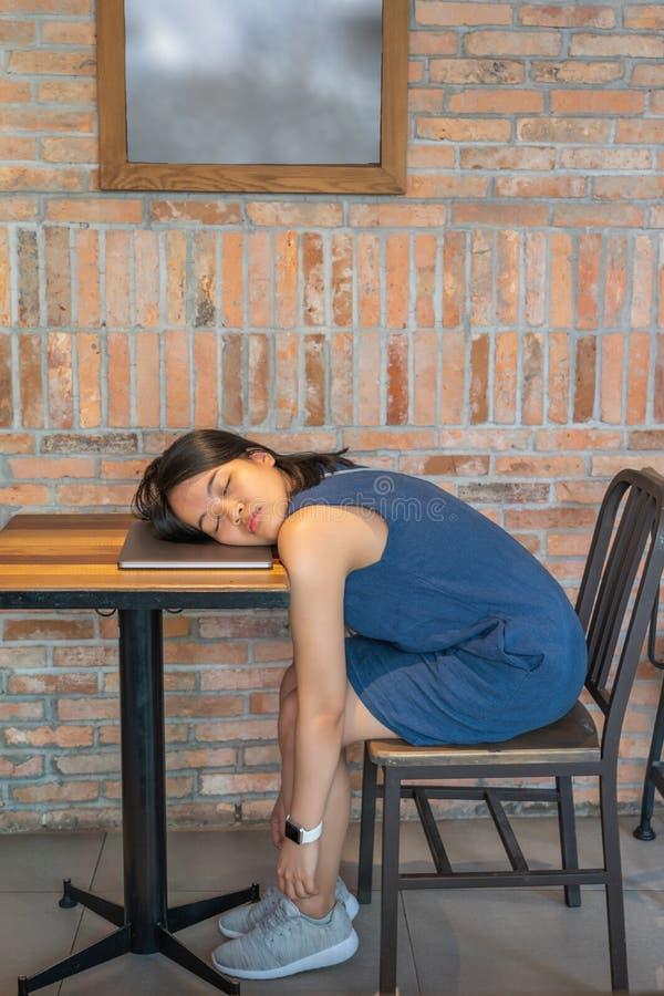 Il giovane asiatico femminile cade addormentato sul suo computer portatile sulla tavola fotografie stock