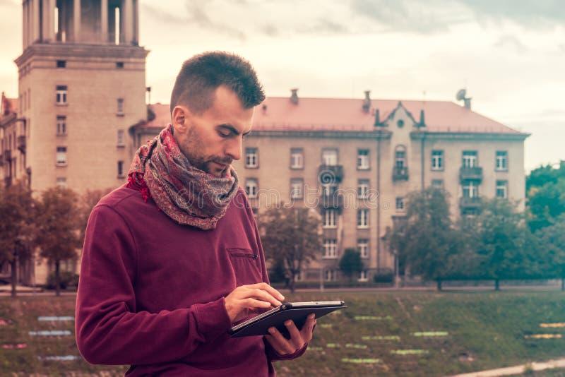 Il giovane astuto lavora al computer della compressa all'aperto nello spazio pubblico urbano immagine stock