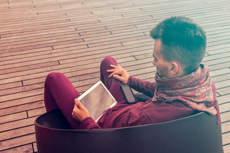 Il giovane astuto lavora al computer della compressa all'aperto nello spazio pubblico urbano immagini stock libere da diritti