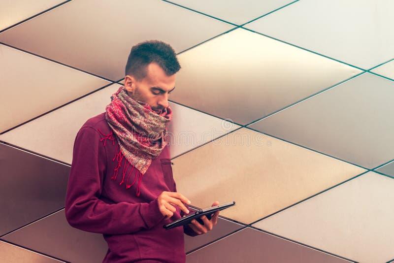 Il giovane astuto lavora al computer della compressa all'aperto nello spazio pubblico urbano fotografie stock libere da diritti