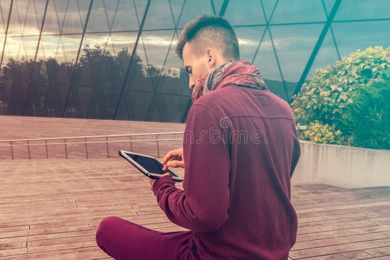 Il giovane astuto lavora al computer della compressa all'aperto nello spazio pubblico urbano immagine stock libera da diritti