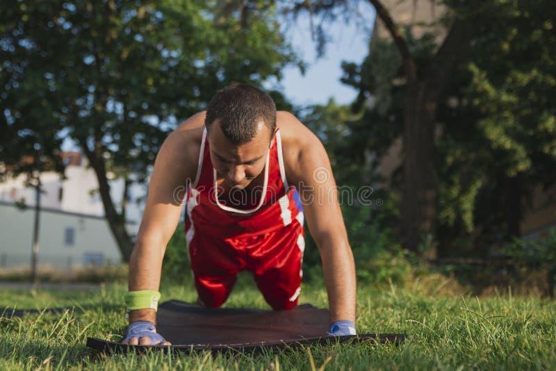 Il giovane atleta esegue il riscaldamento prima della spremuta di formazione dal Th immagini stock