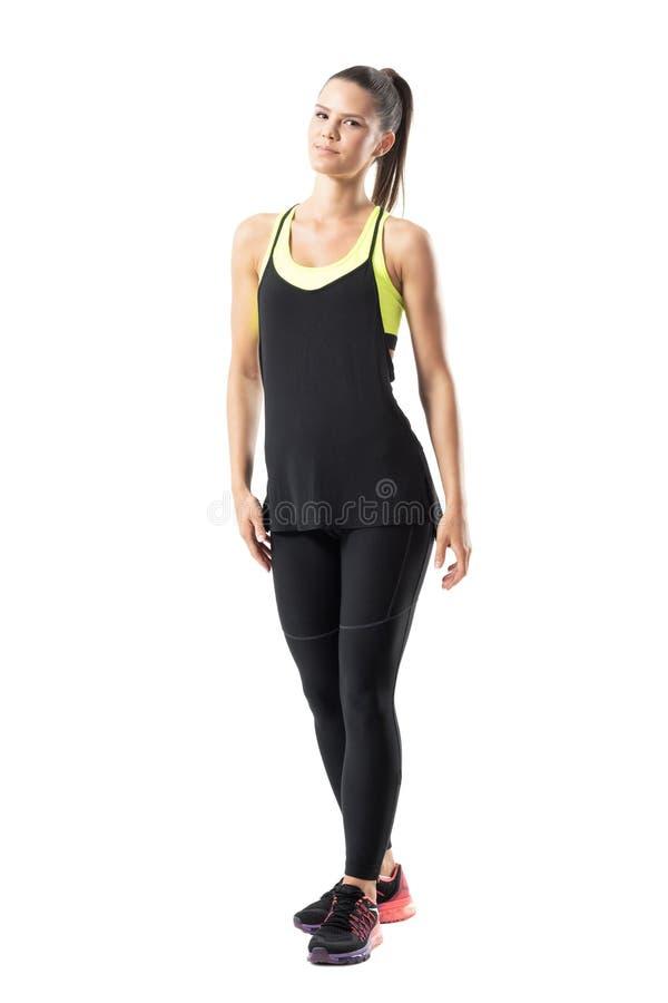 Il giovane atleta femminile contento rilassato nel nero mette in mostra l'abbigliamento che posa alla macchina fotografica fotografie stock