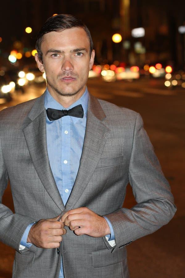 Il giovane attraente alla notte con la città si accende dietro lui, il rivestimento elegante d'uso del vestito e la cravatta a fa immagine stock