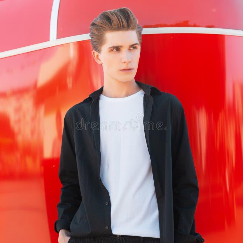 Il giovane attraente con un'acconciatura alla moda in una camicia nera d'annata in una maglietta bianca sta immagine stock