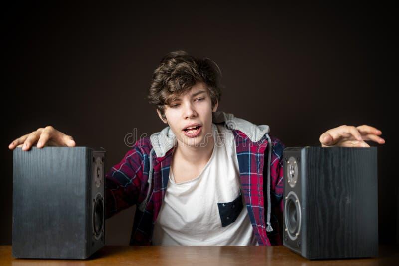 Il giovane audiophile ascolta musica rumorosa dagli altoparlanti f fotografia stock