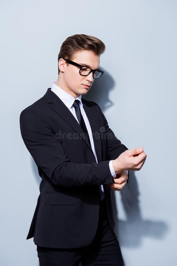 Il giovane avvocato bello dell'uomo d'affari in un vestito sta riparando il suo cuffl fotografia stock libera da diritti