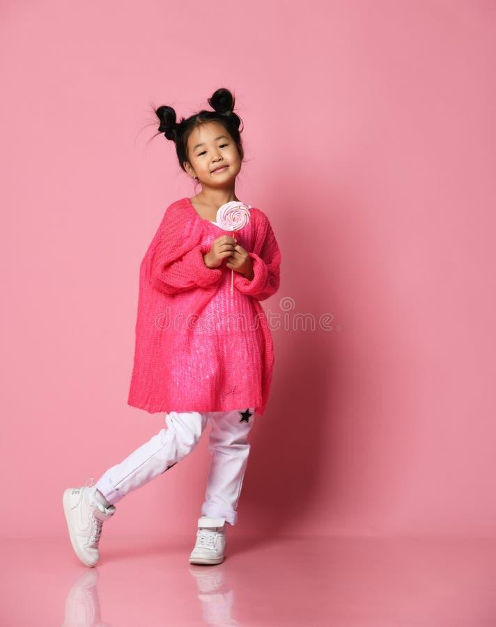 Il giovane bambino asiatico felice della bambina lecca mangia la grande caramella dolce felice del lollypop sul rosa immagine stock