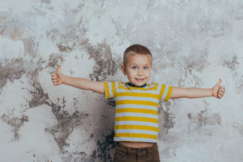 Il giovane bambino del ragazzo in una maglietta a strisce gialla che celebra una risata sorridente felice con una mano si diffond immagine stock libera da diritti