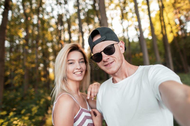 Il giovane bello alla moda con una donna felice in vestiti alla moda dell'estate con i vetri in un cappuccio cammina nella forest fotografia stock