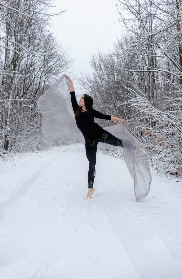 Il giovane bello balletto della ragazza della donna si presenta nella foresta nevosa dell'inverno ed i balli sulla cima del dito  fotografie stock