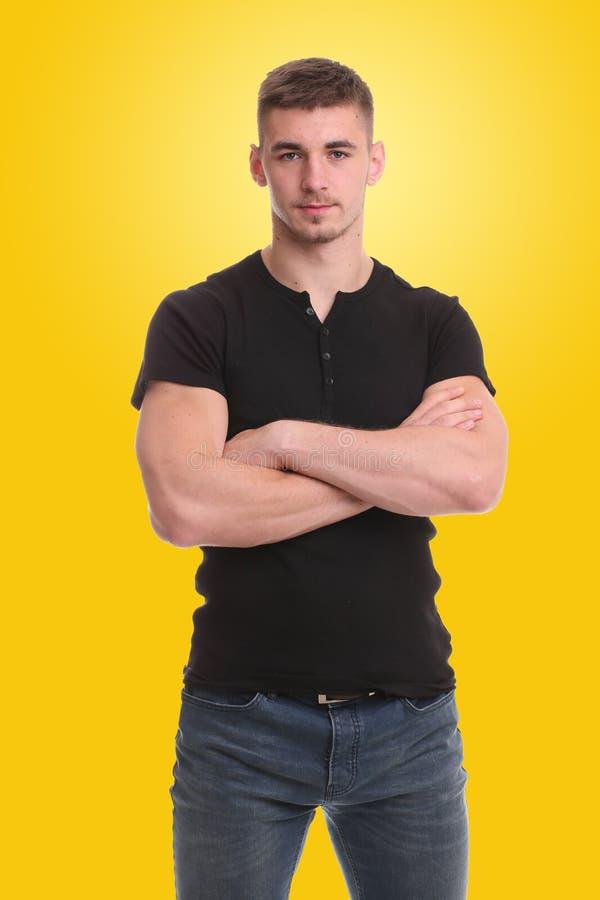 Il giovane bello che sta con le armi ha ripiegato il fondo giallo immagini stock libere da diritti
