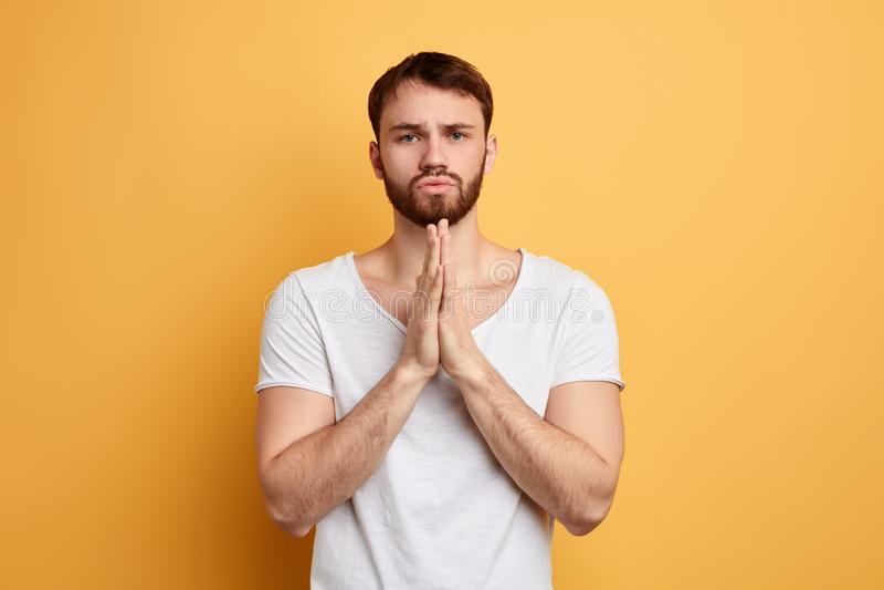 Il giovane bello con la supplica dell'espressione di supplica, tiene insieme le palme fotografia stock