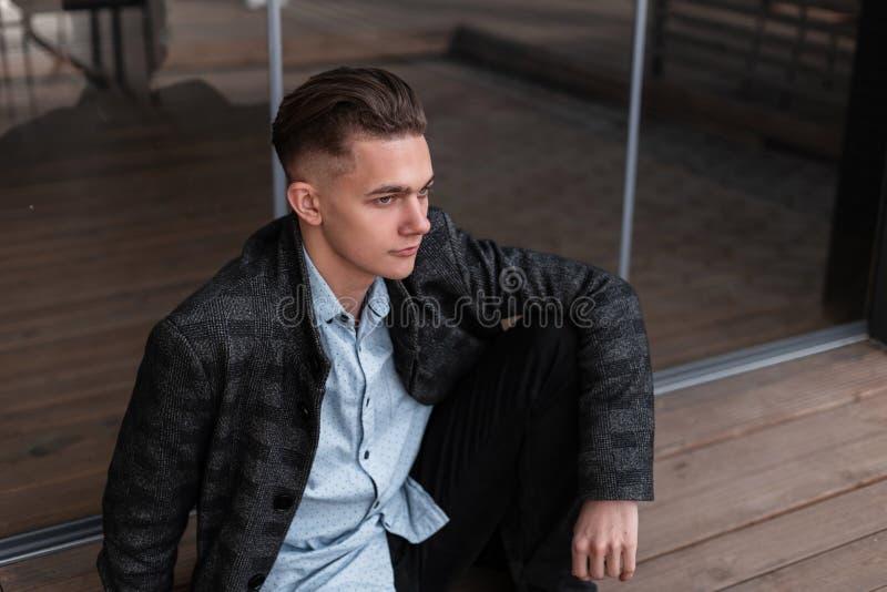 Il giovane bello con un'acconciatura alla moda in un rivestimento d'annata del plaid in una camicia d'avanguardia in jeans sta ri fotografie stock