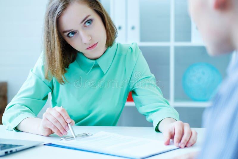 Il giovane bello impiegato femminile dell'agenzia di assunzione di personale contribuisce a compilare la forma al cercatore di la immagine stock libera da diritti