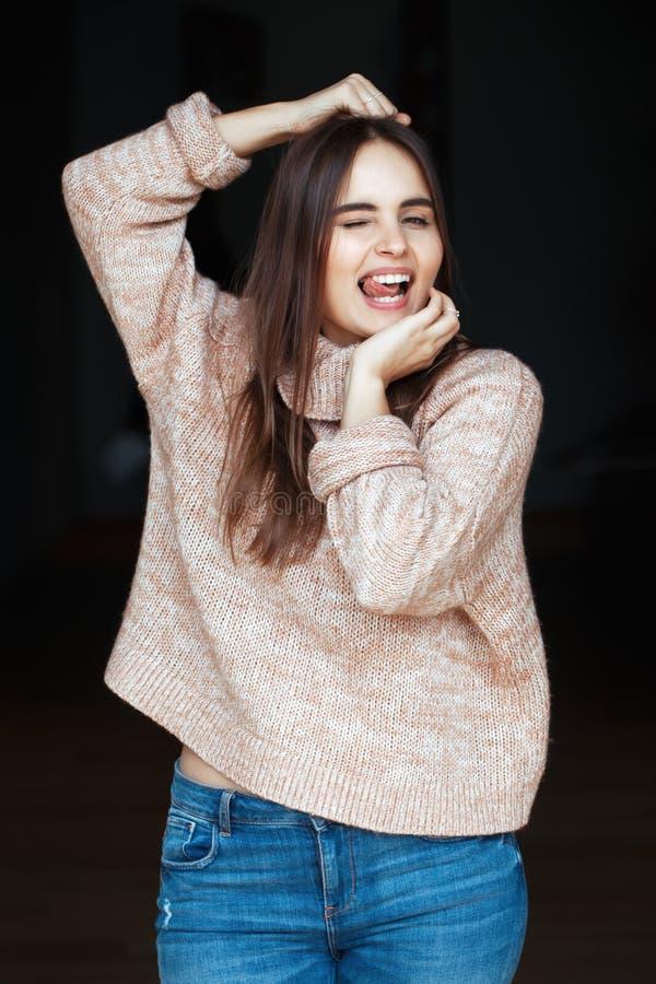 Il giovane bello modello castana caucasico della donna della ragazza con capelli scuri lunghi e marrone osserva in dolcevita e bl immagine stock