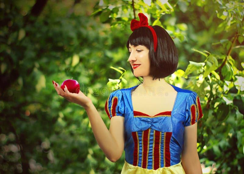 Il giovane bello primo piano bianco come la neve tiene una mela avvelenata rosso contro lo sfondo degli alberi nella foresta fotografie stock