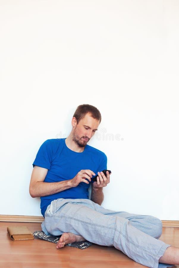 Il giovane bello si diverte al fondo bianco luminoso della parete fotografia stock