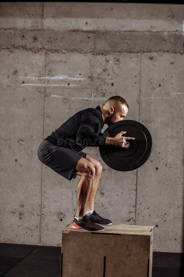 Il giovane ben fatto sta andando saltare sul pavimento esercizi intensi per le gambe fotografie stock libere da diritti