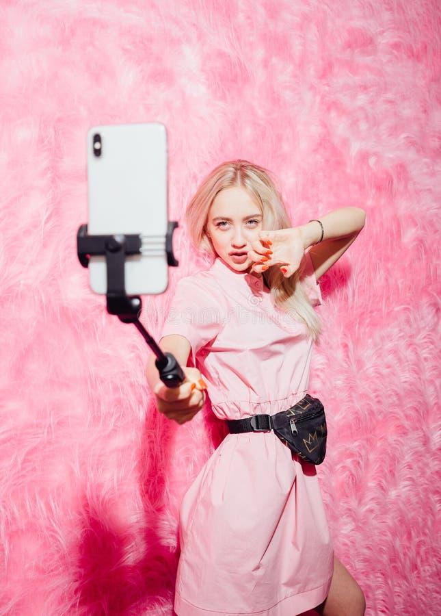 Il giovane blogger grazioso della ragazza vestito in vestito rosa da modo fa un selfie sui precedenti della parete rosa della pel fotografia stock libera da diritti