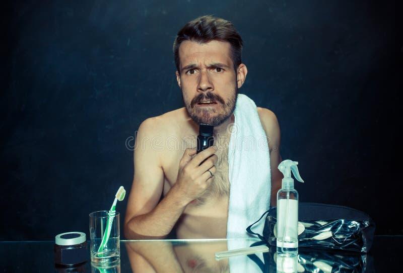 Il giovane in camera da letto che si siede davanti allo specchio che graffia la sua barba fotografia stock