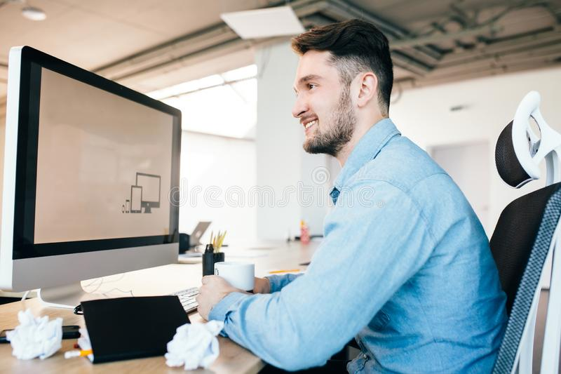 Il giovane in camicia blu sta sedendosi nel suo luogo di lavoro in ufficio Porta la camicia blu Tiene una tazza ed i sorrisi a Th fotografie stock