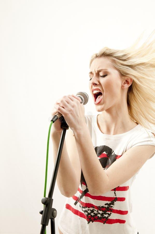 Il giovane cantante attraente effettua con passione fotografia stock