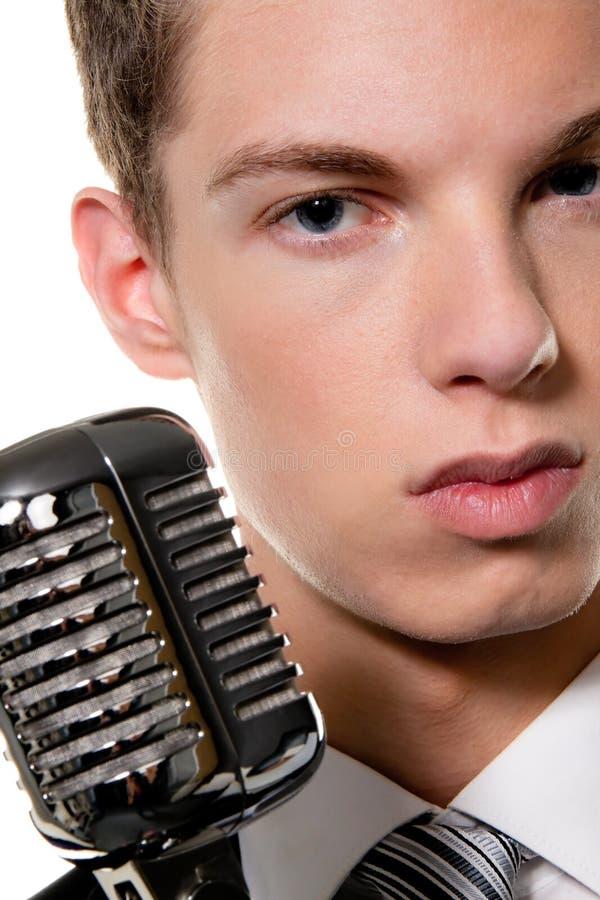 Il giovane cantante con il retro mic canta il karaoke fotografia stock libera da diritti