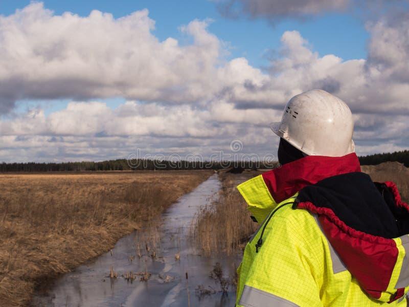 Il giovane caporeparto At Construction Site sta ispezionando la produzione in corso nelle circostanze fredde difficili fotografia stock libera da diritti