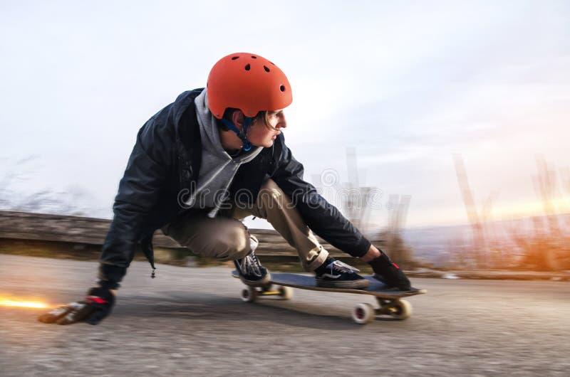 Il giovane in casco sta andando fare scorrere, fare scorrere con le scintille su un longboard sull'asfalto fotografia stock