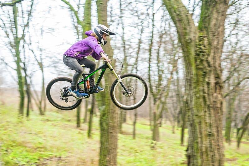 Il giovane cavaliere alla ruota del suo mountain bike fa un trucco in J immagini stock