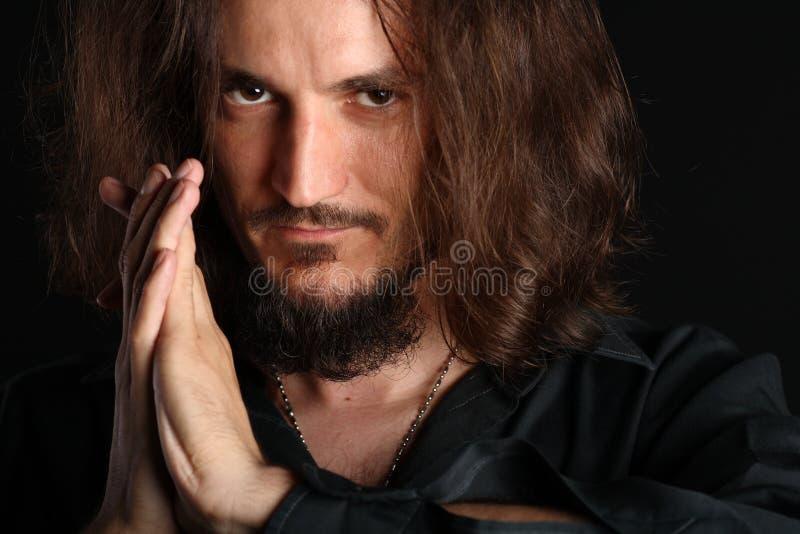 Il giovane che prega e che esamina la macchina fotografica ha isolato la o fotografie stock libere da diritti