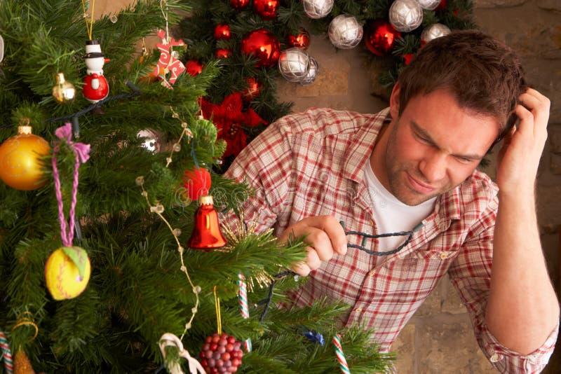 Il giovane che prova a riparare l'albero di Natale si illumina immagine stock