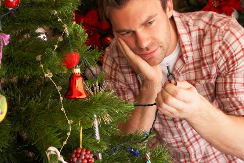 Il giovane che prova a riparare l'albero di Natale si illumina fotografia stock libera da diritti