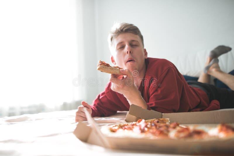 Il giovane che si trova a casa su un sofà con una scatola di pizza, morde un pezzo di pizza con i suoi occhi chiusi ed ottiene il immagine stock