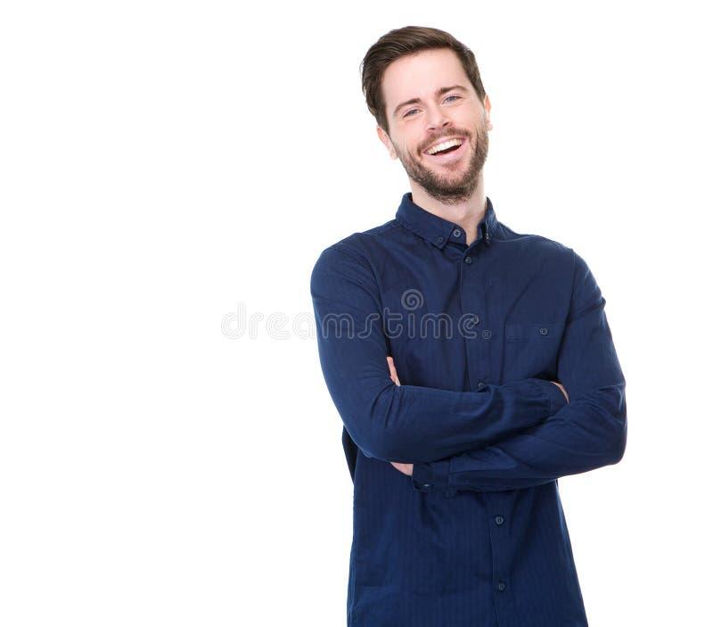 Il giovane che sorride con le armi ha attraversato su fondo bianco fotografia stock