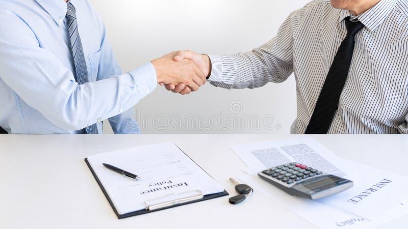 Il giovane che stringe le mani con un agente immobiliare dell'agente di assicurazione o dell'esperto finanziario dopo la firma de immagini stock